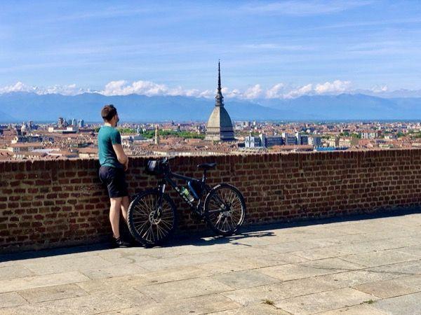 Rowerzysta patrzy na panoramę Turynu z Monte dei Cappuccini