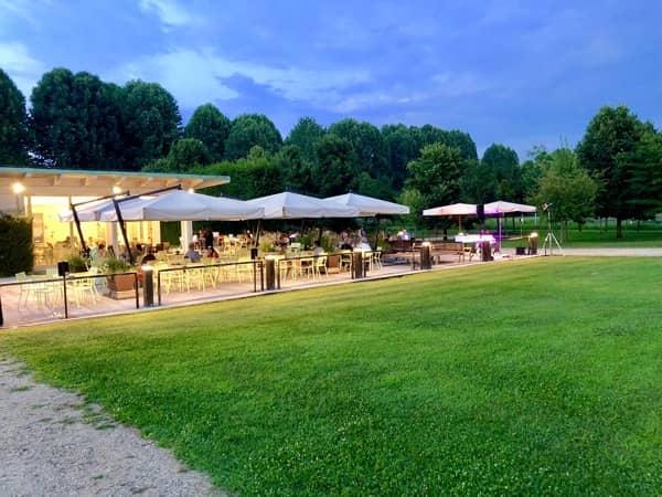Parasole i stoliki barowe na otwartym powietrzu gdzie goście jedzą aperitivo we Włoszech